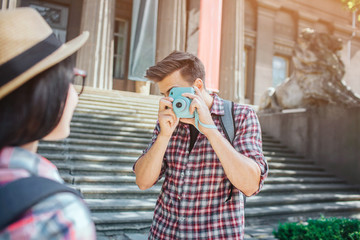 Young male tourist stand at steps and take pictures of woman. He holds blue camera in hands. Man is serious and concentrated. She poses on camera.