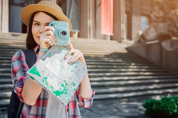 Nice and lovely brunette stand outside. Traveller holds blue camera and poses. Also she has map in hands. Young woman has hat on head.