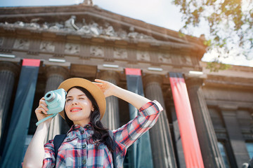Attractive young female traveller stand on street and smiles. Sheholds on hand on hat. Another one has blue camera. She is very positive.