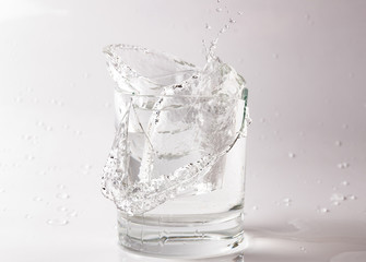 Falling and crashing glass of water. Shards of glass and splashing water