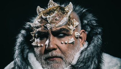 Demon head with thorns on face isolated on black background. Creepy winter spirit, Jack Frost. Closeup portrait of man with fancy make-up wearing white fur coat