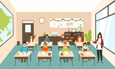 Pupils sitting at desks in modern classroom, young female teacher teaching them. Elementary school boys and girls studying on lesson in class. Colorful vector illustration in flat cartoon style.
