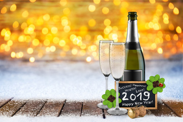 champagne bottle and glasses four leaf clover ladybug cork and blackboard happy new year 2019 greetings in front of bright golden warm bokeh lights snowy snow background wooden floor
