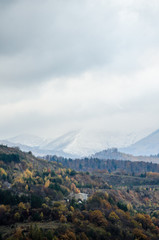 Contrast between autumn hills and snow covered high mountains
