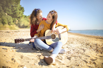 Mother and daughter singing and playing guitar at the beach