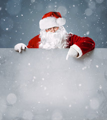 Santa Claus pointing on blank advertisement banner with copy space