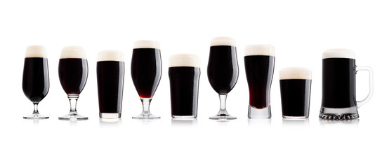 Cold glass of dark stout beer with foam and dew