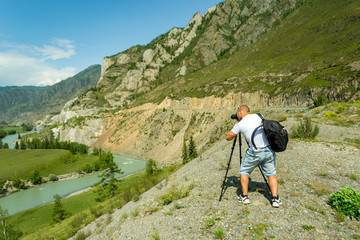 Young man photographer travels through the Altai with the camera on the tripod takes a shot of the snow-covered mountains and the rocks with turquoise winding river Katun. Photo tour.