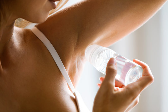 Young attractive woman in white underwear using deodorant roll on in bathroom.