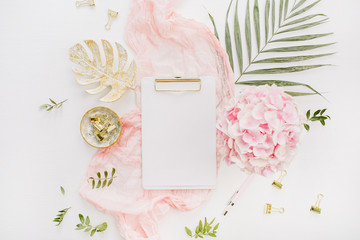 Blank paper clipboard, pink hydrangea flowers bouquet, tropical palm leaf, pastel blanket, monstera leaf plate and accessories on white background. Flat lay