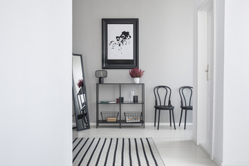 Map in black frame above metal shelf in the waiting room of modern office, real photo with copy space