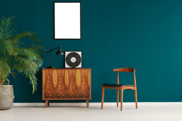 Mockup poster on pine green wall in scandinavian minimal interior with retro furniture and plant, real photo