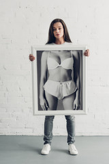 young transgender man holding black and white photo with female body in underwear in front of white brick wall
