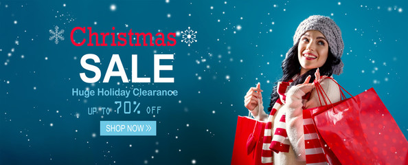 Christmas sale message with young woman holding shopping bags