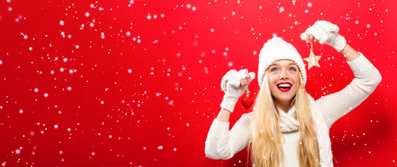 Happy young woman holding a Christmas ornament