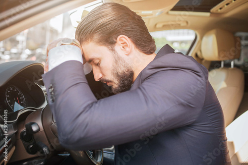 Tired And Exhausted Young Businessman Sits On Car Leans To Steering Wheel He Keeps Eyes Closed Man Sleeping