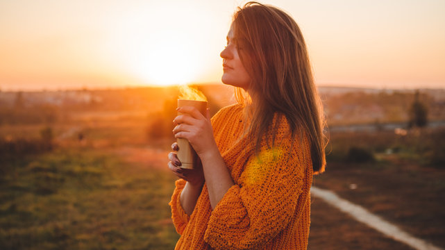 Young woman  in a orange sweater with thermos thermo cup outdoor portrait in soft sunny daylight. Autumn. Sunset. Cozy