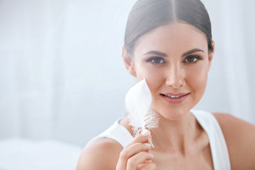 Beauty Skin Care. Woman Touching Soft Face Skin With Feather