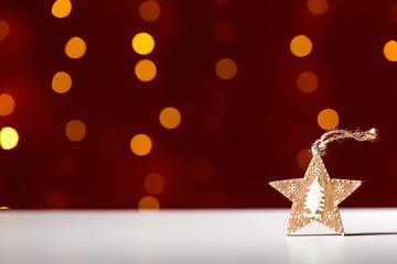Christmas star ornament on a shiny light dark red background