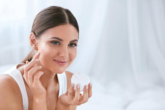 Beauty. Beautiful Woman Applying Face Cream On Soft Facial Skin