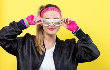 Woman in 1980's fashion with shatter shade glasses on a yellow background Wall mural