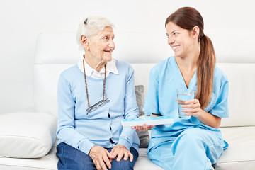 Wall Mural - Weiblicher Pfleger gibt Seniorin ein Medikament