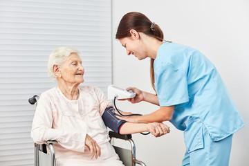 Wall Mural - Pflegekraft macht Blutdruckmessung bei Patientin