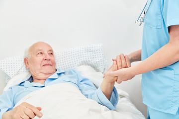 Kranker Senior liegt im Bett im Pflegeheim