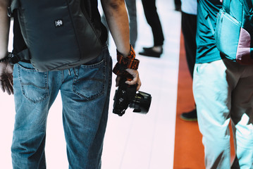 Close up standing unidentified man are holding the DSLR camera with one hand. The man wearing jeans looked from behind with the camera. Photographer hold camera real view