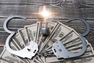 handcuffs, American dollar bills, light bulb on wooden table background. corruption, business fraud, financial crimes.