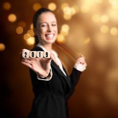 junge lachende Geschäftsfrau vor Silvesterhintergrund hält  Würfel mit der Aufschrift 2019 in die Kamera