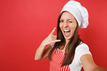 Housewife female chef cook or baker in striped apron, white t-shirt, toque chefs hat isolated on red wall background. Close up housekeeper woman doing taking selfie shot. Mock up copy space concept.