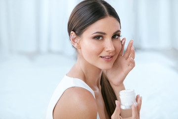 Woman Applying Facial Cream On Face Skin In White Interior
