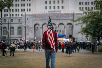 A young man carries an American flag to a protest