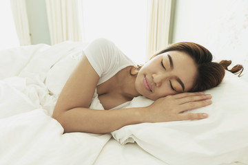 Beautiful Attractive Asian woman sleep and sweet dream on bed in bedroom in the morning,Healthcare Concept,Warm Tone