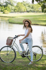 Brunette girl with bicycle in park