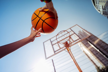 City activity. Active teenager raising hands while playing basketball