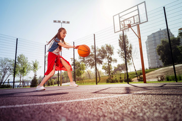 Be active. Kind teenager expressing positivity while playing basketball