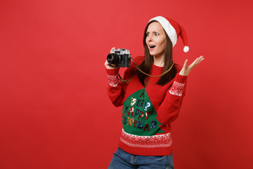 Amazed young Santa girl hold retro vintage photo camera, keeping mouth wide open, spreading hands isolated on red background. Happy New Year 2019 celebration holiday party concept. Mock up copy space.