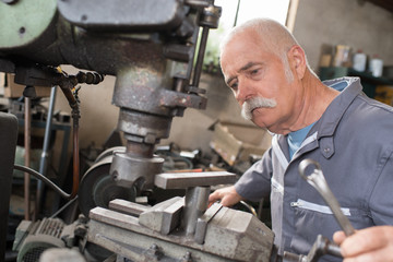 elderly worker watches processing of detail on milling machine