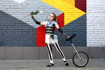 Wall Mural - Pretty girl clown with white rose and a unicycle