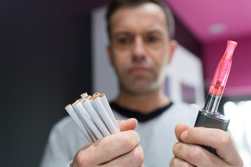 man is holding vaporizer and conventional tobacco cigarettes