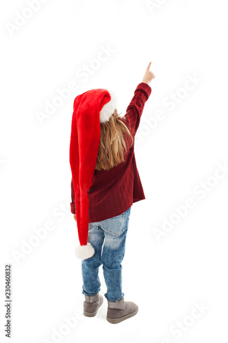 e9eed278f18 Back view of little girl in red Santa hat pointing at wall. Rear view.  Isolated on white background