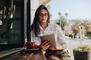 Woman sitting at a cafe working on digital tablet