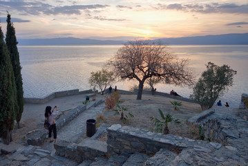 Young woman taking photos of the sunset from the church of Jovan Kaneo