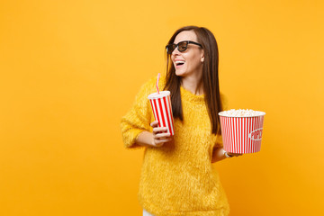 Joyful young woman in 3d imax glasses looking aside watching movie film hold bucket of popcorn, plastic cup of cola or soda isolated on yellow background. People sincere emotions in cinema, lifestyle.