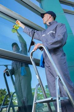 man cleaning window ouside an office