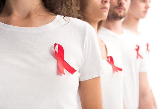 cropped image of people standing with red ribbons on white shirts isolated on white, world aids day concept