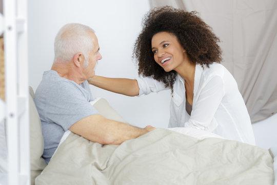 senior patient receiving help from female nurse