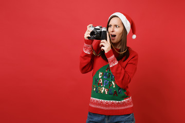 Shocked young Santa girl taking pictures on retro vintage photo camera, keeping mouth wide open isolated on red background. Happy New Year 2019 celebration holiday party concept. Mock up copy space.